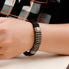 Кожаный браслет на двух жгутах и декорированный жгутом веревки и стальными втулками по бокам
